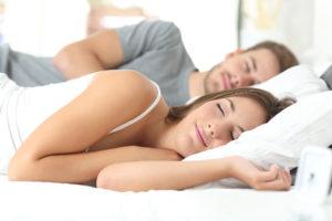 Glückliches Paar schläft im Bett